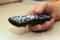 TV remote controller in the man`s hand on light textile backgtround with empty copyspace Royalty Free Stock Photos