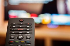 TV Remote with Dedicated Netflix Button in front of Defocused Smart TV royalty free stock images