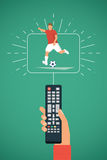 TV remote in hand. Football / Soccer player kick on ball. Sport broadcasting theme. Stock Images