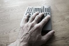 Tv remote in hand Royalty Free Stock Photography