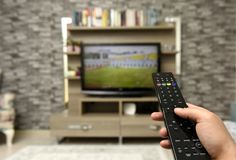 Tv remote in my hands and a televison. Shot Royalty Free Stock Photos