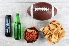 TV Remote, Salsa, Beer, Chips and Football Stock Photo
