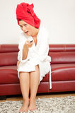 Tv remote towel pampered woman. Red towel pampered woman switching channel while sitting on red leather sofa smiling in to camera while watching tv and holding Royalty Free Stock Photos
