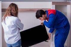 Tv repairman technik naprawia tv w domu obraz stock