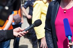Journalist holding microphone conducting television interview. TV reporter holding microphone conducting television interview Stock Images