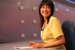 TV reporter in studio. Young woman TV reporter smiling and looking back while preparing for the news presenting royalty free stock photos
