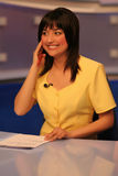 TV reporter in studio. Young woman TV reporter smiling and listening in earphone while preparing for the news presenting royalty free stock image