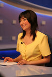 TV reporter in studio. Young woman TV reporter, smiling and presenting the news royalty free stock image