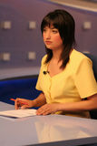 TV reporter in studio. Young woman TV reporter presenting the news stock photos