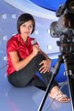 TV reporter in studio. TV reporter with microphone taking an interview Stock Photo