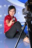 TV reporter in studio. TV reporter with microphone showing the finger Stock Photography