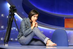 TV reporter in studio. Young woman reporter posing like a photo model in TV studio royalty free stock photos