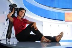 TV reporter in studio. Young woman reporter posing like a photo model in TV studio Stock Image