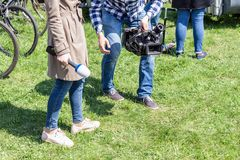 TV reporters working outdoors. Journalsit and cameraman making report at street on bright sunny day.  royalty free stock photos