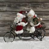 Två roliga Santa Claus på en tandemcykel i brådskan för att shoppa för jul Arkivfoto