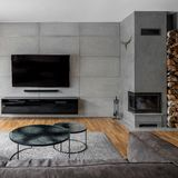 Tv room with cement wall. Tv living room with cement wall and wall mounted fireplace stock photo