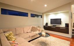 TV room. A comfortable and modern TV room with L-shaped couch Stock Image
