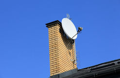 Tv satellite dish on  chimney. Royalty Free Stock Images
