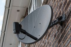 TV satellite dish on a brick wall stock image