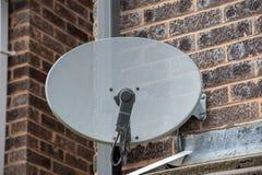 TV satellite dish on a brick wall. TV satellite dish mounted on a brick wall stock image