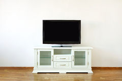 TV set on the stand. Large widescreen TV set on the white dresser in a bright room Stock Photo