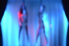 Två sexiga strippor, suddighetseffekt utan fokus - som bakgrund Arkivfoto