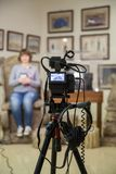 TV shooting at the Museum. LCD monitor on the camcorder. The girl in front of the camera. A record of the interview. Filming equipment and lighting equipment Royalty Free Stock Photography