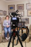 TV shooting at the Museum. LCD monitor on the camcorder. The girl in front of the camera. A record of the interview. Filming equipment and lighting equipment Royalty Free Stock Photo