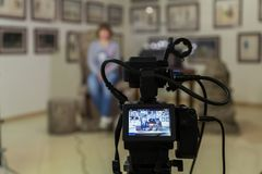 TV shooting at the Museum. LCD monitor on the camcorder. The girl in front of the camera. A record of the interview Royalty Free Stock Image