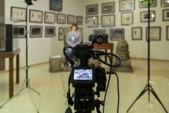 TV shooting at the Museum. LCD monitor on the camcorder. The girl in front of the camera. A record of the interview Stock Photo