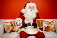 TV show. Traditional Santa Claus sitting on the couch watching TV, eating popcorn and drinking soda. Christmas. Red background Stock Photos