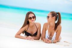 Två sinnliga kvinnor i bikini på en strand Arkivfoto