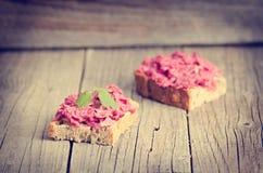 Två skivor av bröd på en trätabell med rödbeta fördelade Naturlig bakgrund och sund, vegetarian- och strikt vegetarianmat Snabb b Royaltyfri Fotografi