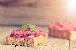 Två skivor av bröd på en trätabell med rödbeta fördelade Naturlig bakgrund och sund, vegetarian- och strikt vegetarianmat Snabb b Royaltyfri Bild