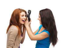 Två skratta tonåringar som delar hörlurar Arkivbild