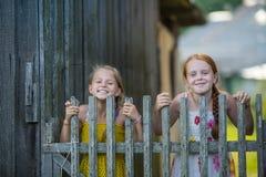 Två små flickor som har gyckel som poserar nära ett lantligt trästaket Lyckligt Arkivbild