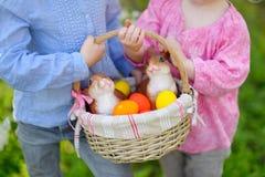 Två små flickor som rymmer en korg av påskägg Royaltyfri Fotografi