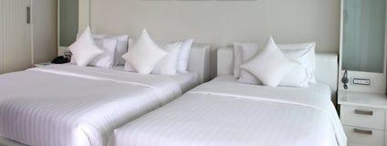 Två sängar med vita överkast och kuddar Royaltyfri Bild