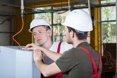 Två specialister som reparerar fabriksmaskinen Fotografering för Bildbyråer