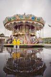 Två söta barn, pojkebröder, hållande ögonen på karusell i regnet, Royaltyfria Foton