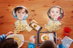 Två söta barn, pojkebröder och att ha för lunchspagetti på Royaltyfria Bilder