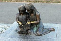 Två statyetter, stående läsning på en parkera Royaltyfri Bild