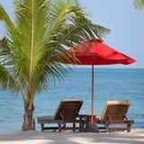 Två strandstolar, rött paraply och palmträd på stranden i Thailand Royaltyfri Bild