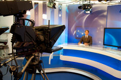 TV Studio. Reporter presenting news in TV studio - Focus on Camera Stock Photography