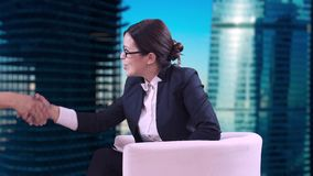 The TV Studio. Closeup of brunette in glasses. She sits in the Studio in a business suit and interviews. Smiles and stock video footage