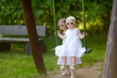 Två systrar som har gyckel på en gunga på sommardag Fotografering för Bildbyråer