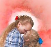 Två systrar som omfamnar och kysser Arkivfoto