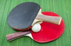Två tappningbordtennisracket och knackar pongbollar Royaltyfri Fotografi