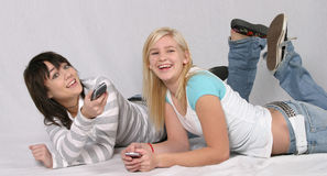 TV Teens. Smiling brunette and blonde teen girls laying on floor watching TV Stock Image