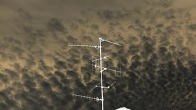 TV Television aerial antenna majestic cirrocumulus clouds. Black sky majestic cirrocumulus clouds on a summer afternoon with TV Television aerial antenna in the stock footage